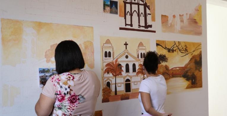 Artista faz pinturas ilustrativas na sala de recepção da Secretaria de Turismo
